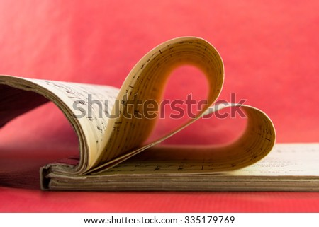 Music notation book with pages shaping heart closeup - stock photo