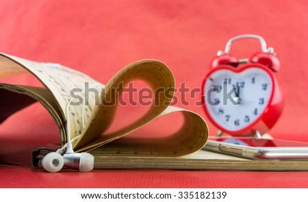 Music notation book with pages shaping heart, with smartphone and earphones - stock photo
