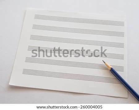 Music note sheet with pencil on white background, Selective focus on Sharpness of pencil - stock photo