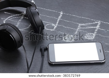 Music notes with treble clef, smartphone  and headphones, copy space on screen - stock photo