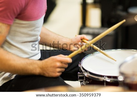 music, people, musical instruments and entertainment concept - male musician playing cymbals and pointing drumstick to you at music store - stock photo