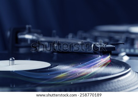 Music player playing vinyl music with colourful abstract lines concept on background - stock photo