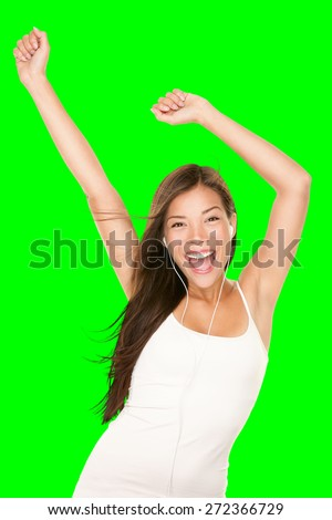 Music player woman dancing with earphones. Girl happy and joyful listening to music wearing earphones. Portrait of cheerful Chinese Asian / Caucasian female model isolated cutout on green background. - stock photo