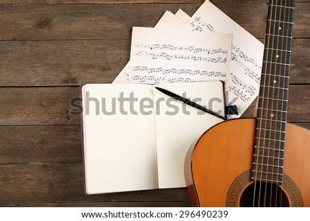 Music recording scene with guitar, notebook and music sheets on wooden table, closeup - stock photo
