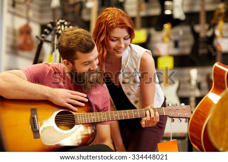 music, sale, people, musical instruments and entertainment concept - happy couple of musicians with guitar at music store - stock photo