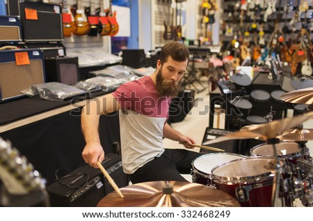 music, sale, people, musical instruments and entertainment concept - male musician playing cymbals at music store - stock photo