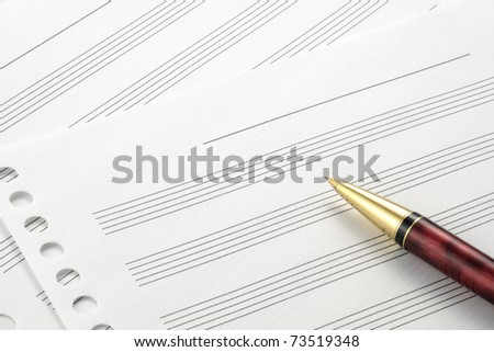 Music score paper and pen - stock photo