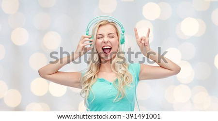 music, technology and people concept - happy young woman or teenage girl with headphones singing song and showing rock gesture over holidays lights background