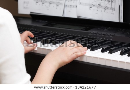 Music time: girl hands girl playing on piano - stock photo