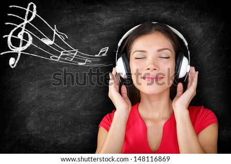 Music - woman wearing headphones listening to music with music notes drawn on black blackboard texture background. Serene relaxing beautiful young multiracial Asian Caucasian girl enjoying music. - stock photo
