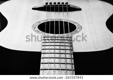 musical background image of acoustic guitar focus on  strings, very shallow depth of field. Black & White. - stock photo