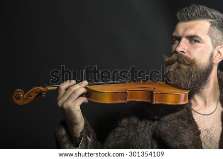 Musical brutal unshaven man with long beard and hendlebar moustache in brown fur coat with collar and chain on chest holding wooden violin standing on black background copyspace, horizontal picture - stock photo
