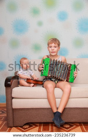 musical ensemble of two brothers - guitar and accordion - stock photo