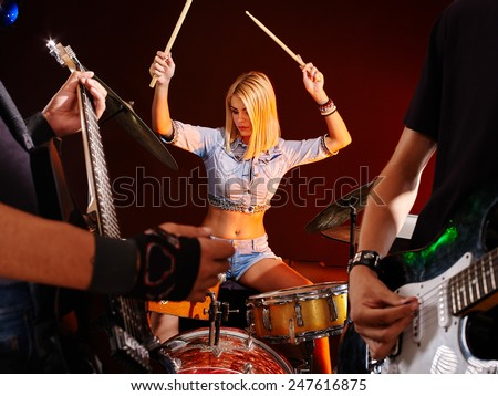 Musical group playing in night club. Girl with drum - stock photo