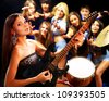 Musical group playing in night club. Male and female. - stock photo