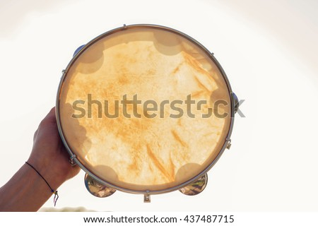 Musical instrument tambourine or pandeiro on a background of the sky at sunset - stock photo