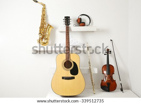 Musical instruments and headphones on decorated shelves against white wall background - stock photo