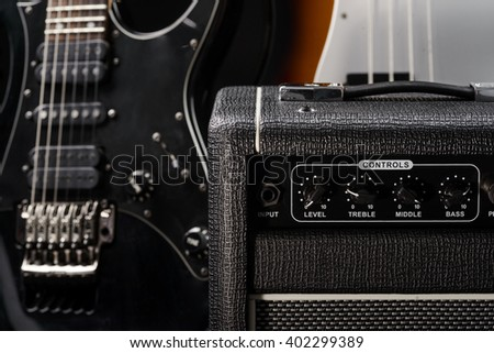 Musical instruments are getting ready for a big storm in a concert hall. Real pleasure for music fans. Electric and bass guitars in background and special amp in a foreground. - stock photo