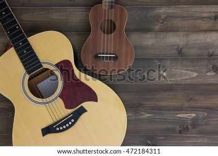 Musical instruments guitar ukulele on old wooden background with copy space. Vintage effect.
