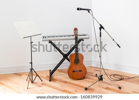 Musical instruments in a room. Electric piano, guitar, microphone and stand with sheet music. - stock photo