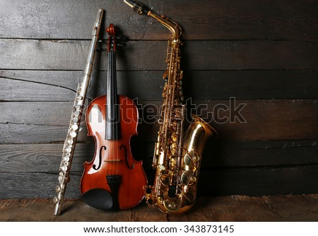Musical instruments: saxophone, violin and flute on wooden background - stock photo