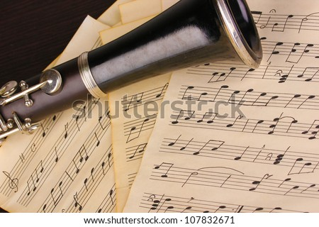Musical notes and clarinet on wooden table - stock photo