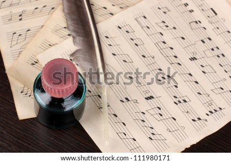 Musical notes and feather on wooden table - stock photo