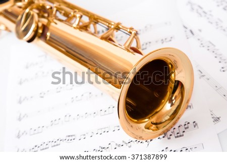 Musical notes and saxophone, isolated on white - stock photo