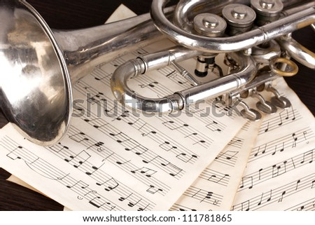 Musical notes and trumpet on wooden table - stock photo