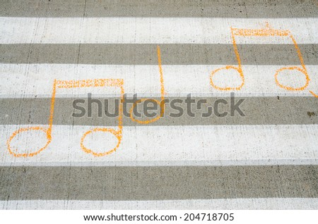 Musical notes creatively drawn on a crosswalk - stock photo