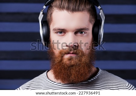 Musical style. Confident young bearded man in headphones standing against stripped background and listening to the music - stock photo