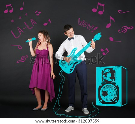 Musical young couple, on black background - stock photo