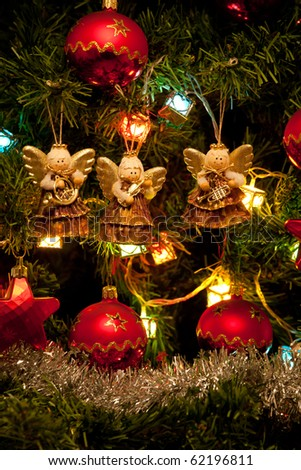 Musician angels hanging on the Christmas tree, vertical close up - stock photo