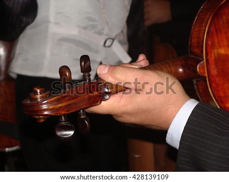 Musician hand holding the violin during the concert.