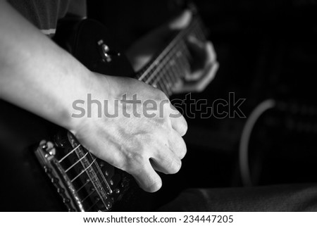 musician hands play electric guitar , focus to right hand & shallow dept of field / black and white processed - stock photo