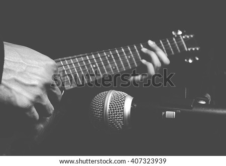 musician hands playing & recording acoustic guitar, isolated on black + BW film filter - stock photo