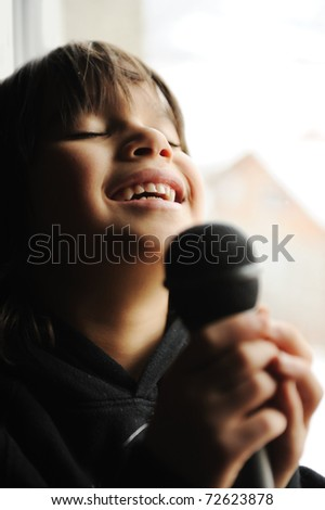 Musician kid singing a song with microphone - stock photo
