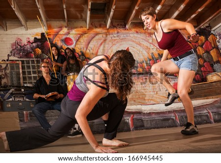 Musician perform while capoeira women practice techniques - stock photo