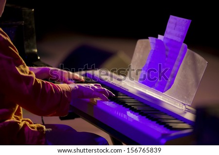 musician playing a keyboard synthesizer during a concert - stock photo