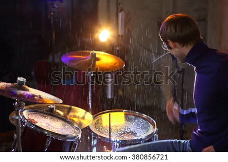 Musician playing drums in the rain in the studio - stock photo