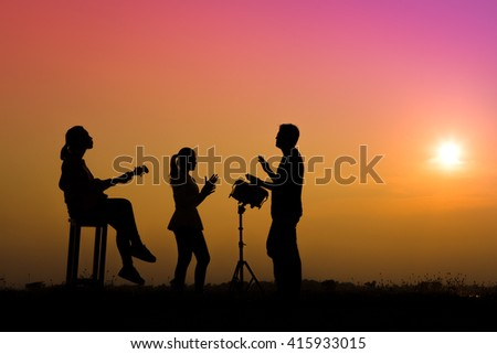musician playing guitar against the background of sunset - stock photo