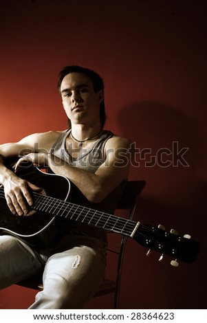 Musician playing guitar on re? background - stock photo