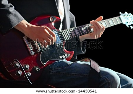 musician playing on guitar on black background - stock photo