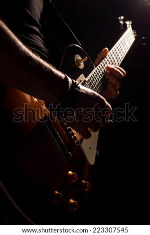 musician playing on guitar on dark background - stock photo