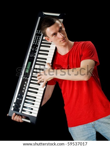musician playing the electronic piano.man on a black background - stock photo