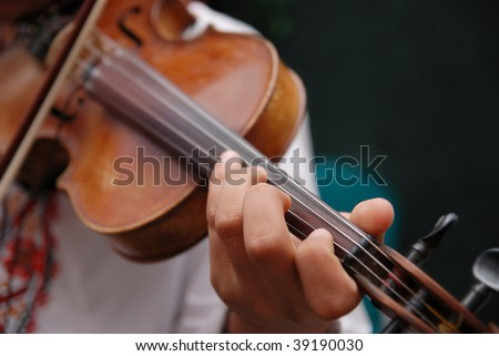 Musician playing the violin, dressed in traditional clothes - stock photo