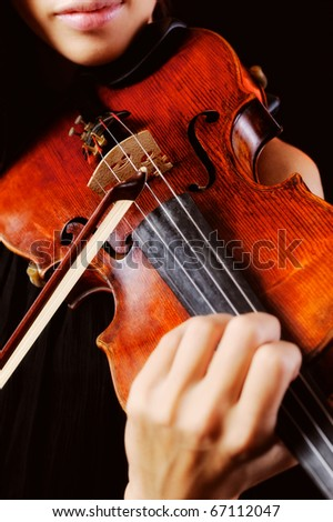 Musician playing violin. Isolated on the black background - stock photo