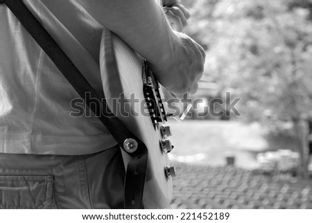 Musician plays his electric guitar during a soundcheck on stage - monochrome processing