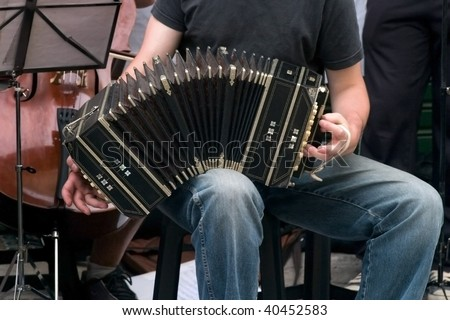 Musician plays tango with bandoneon in the street. - stock photo