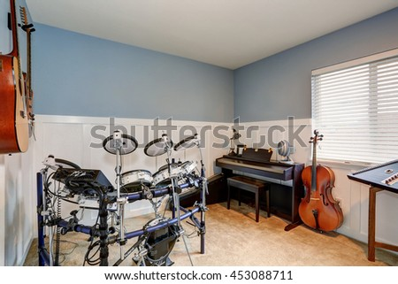 Musician's room interior  with drum set, guitars and piano. Small room with blue walls and beige carpet floor.